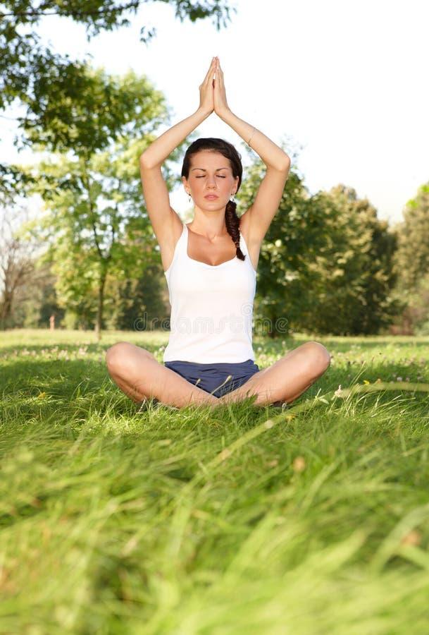 Jeune femme faisant le yoga image stock