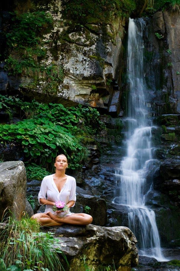 Jeune femme faisant le yoga avec la fleur de lotus photographie stock