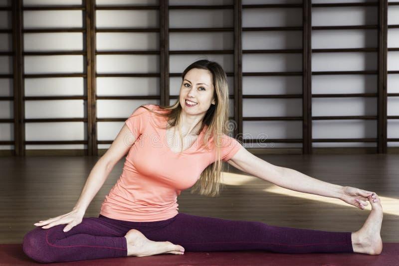Jeune femme faisant le yoga sur la couverture dans le hall image stock