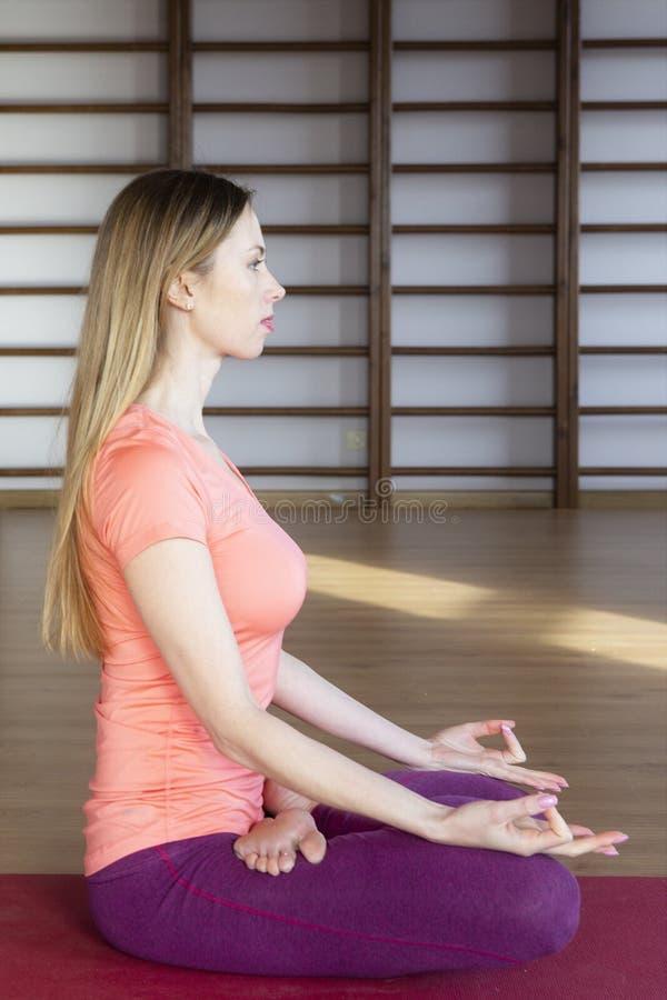 Jeune femme faisant le yoga sur la couverture dans le hall images libres de droits