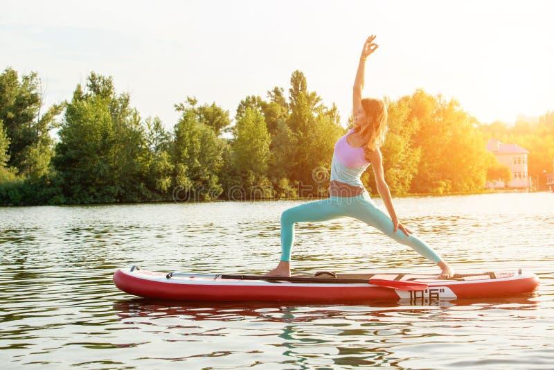 Jeune femme faisant le yoga sur le panneau de petite gorgée avec la palette Pose de yoga, vue de côté - concept d'harmonie avec l photos stock