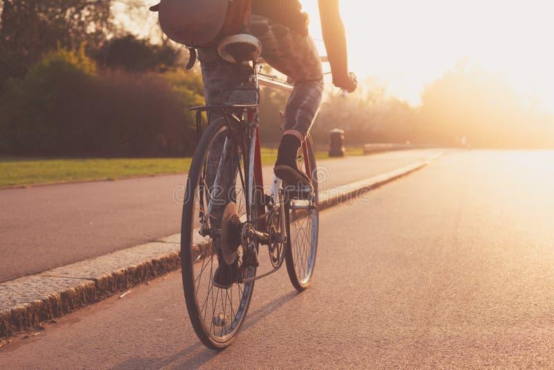 Jeune femme faisant un cycle en parc au coucher du soleil photos libres de droits