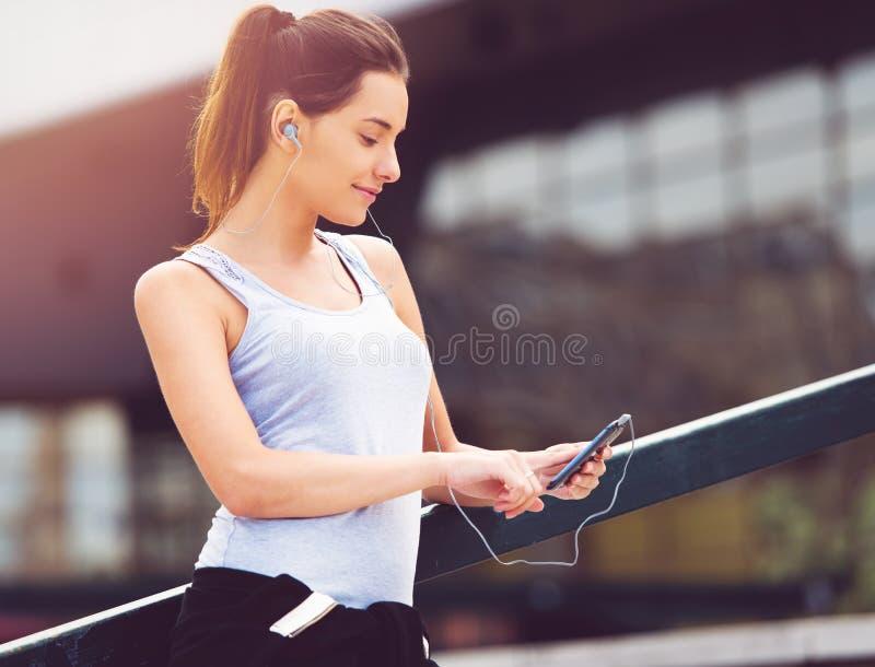 Jeune femme faisant une pause de l'exercice dehors avec le téléphone portable photo libre de droits