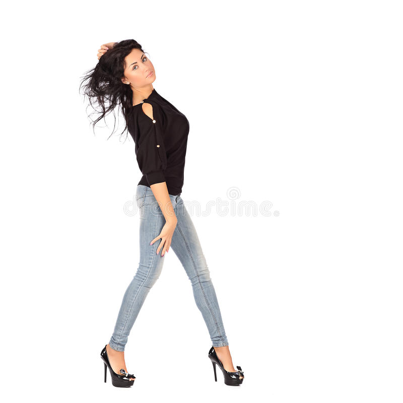 Jeune femme fascinante dans la veste noire et jeance sur le fond blanc photographie stock