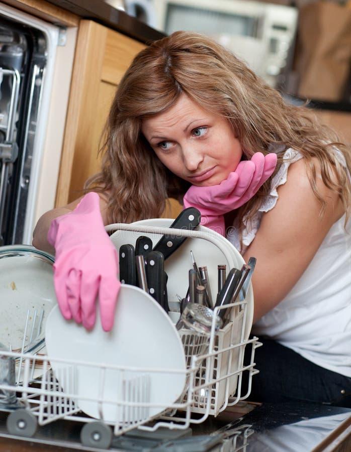 Jeune femme fatigué classant le lave-vaisselle photographie stock