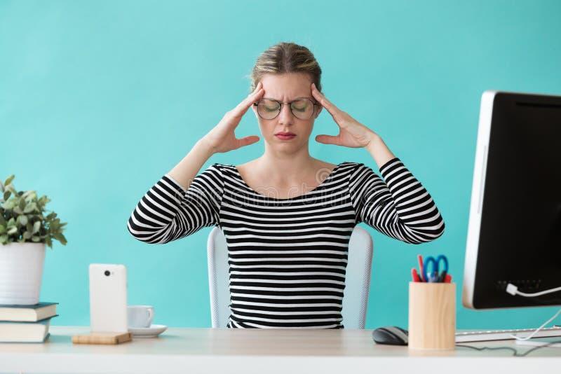 Jeune femme fatiguée d'affaires ayant le mal de tête tout en travaillant avec l'ordinateur dans le bureau photos libres de droits