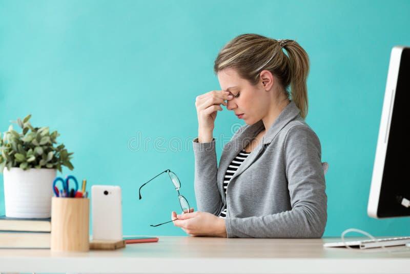 Jeune femme fatiguée d'affaires ayant le mal de tête tout en travaillant avec l'ordinateur dans le bureau photo stock