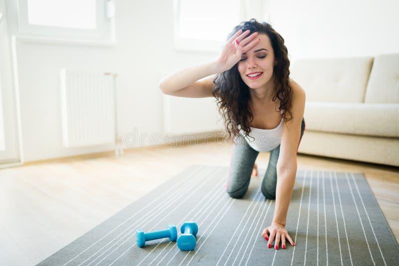 Jeune femme fatiguée de forme physique détendant après la formation photo libre de droits