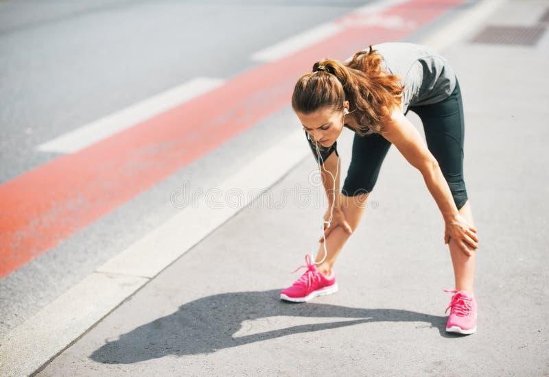 Jeune femme fatiguée de forme physique dehors dans la ville images libres de droits