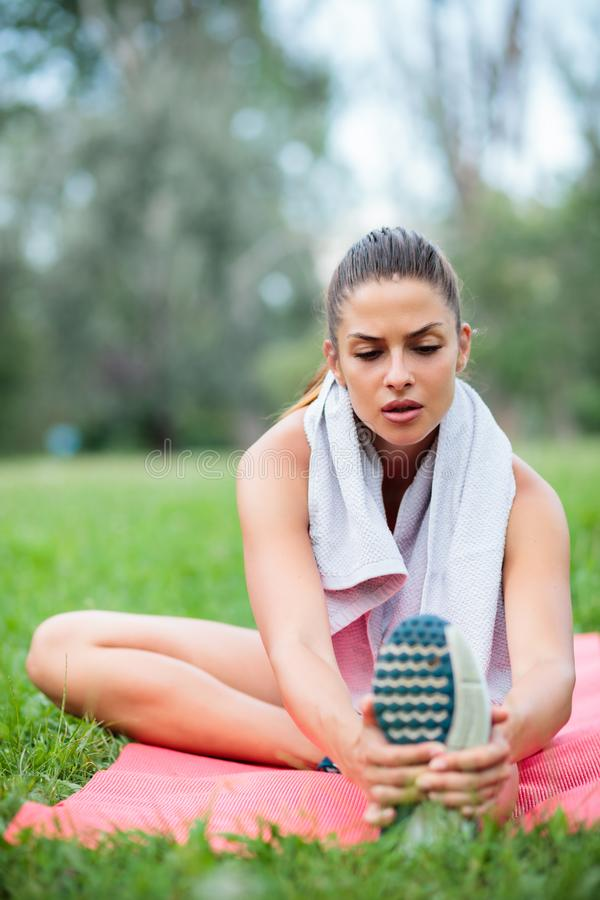 Jeune femme fatiguée s'étirant après une séance d'entraînement en parc image stock