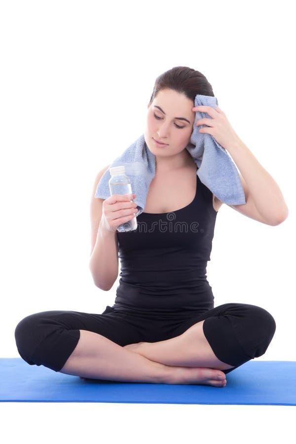 Jeune femme fatiguée s'asseyant avec la bouteille de l'eau minérale d'isolement photos libres de droits
