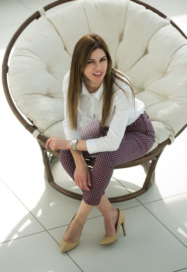 Jeune femme fatiguée s'asseyant dans la chaise ronde confortable photo libre de droits