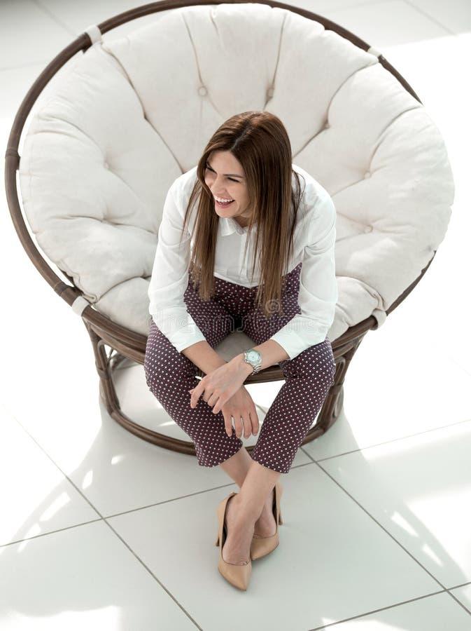 Jeune femme fatiguée s'asseyant dans la chaise ronde confortable photos stock