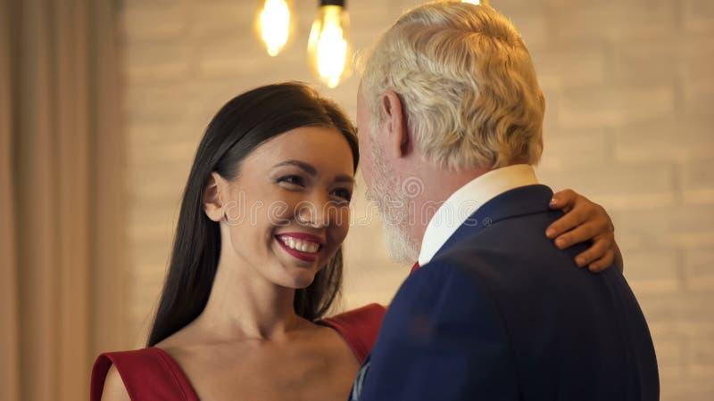 Jeune femme flirtant et dansant avec le vieux millionnaire la date, service d'escorte photos stock