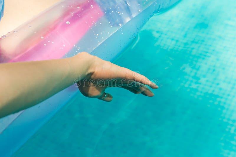 Jeune femme flottant sa main dans la piscine images stock