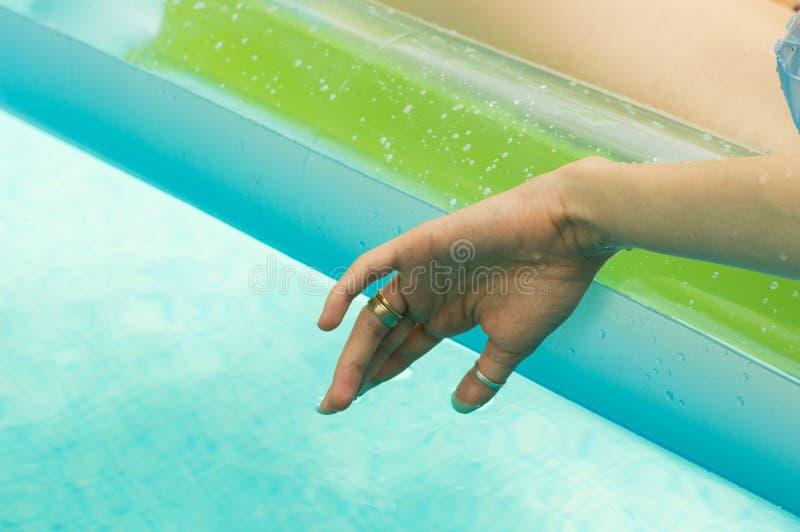 Jeune femme flottant sa main dans la piscine photographie stock