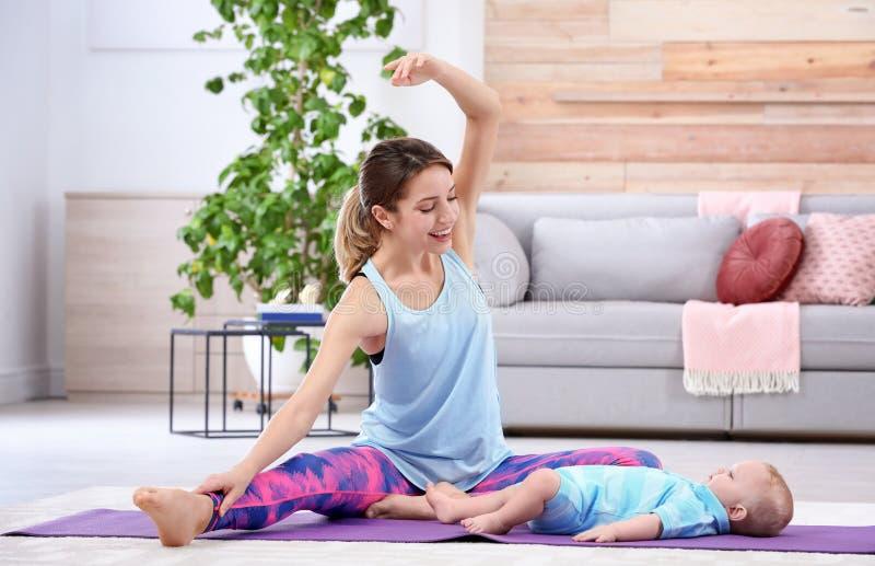 Jeune femme folâtre faisant l'exercice avec son fils à la maison image stock