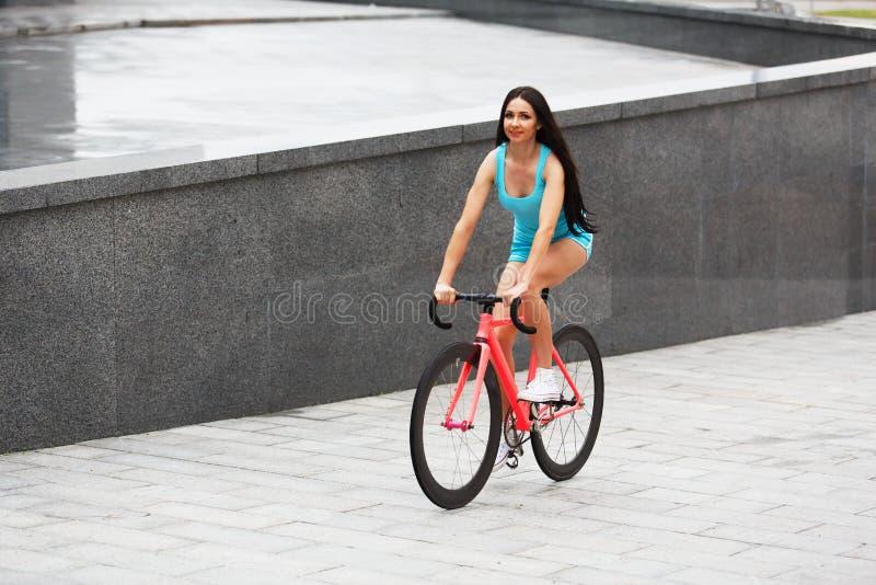 Jeune femme folâtre sexy mince sur la bicyclette image libre de droits
