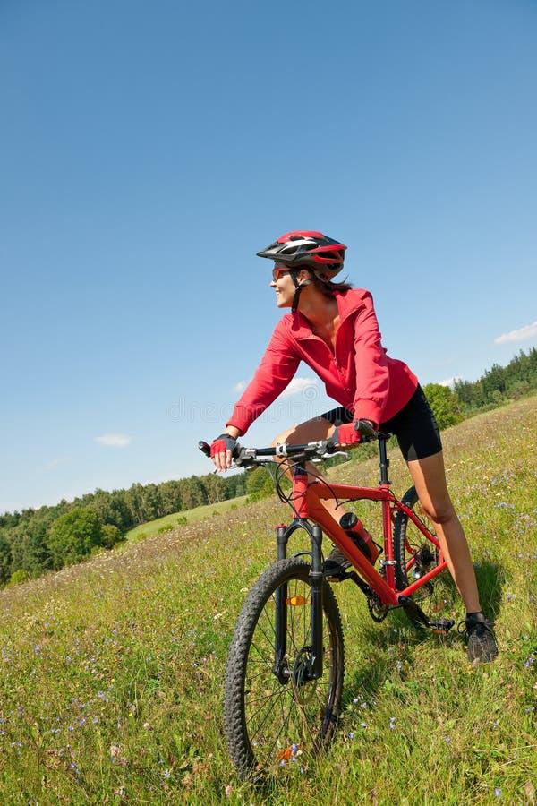 Jeune femme folâtre sur le vélo de montagne images libres de droits