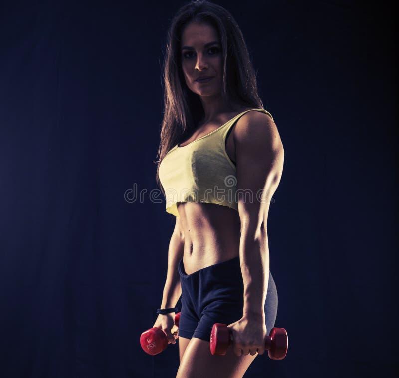 Jeune femme forte avec des haltères photographie stock libre de droits