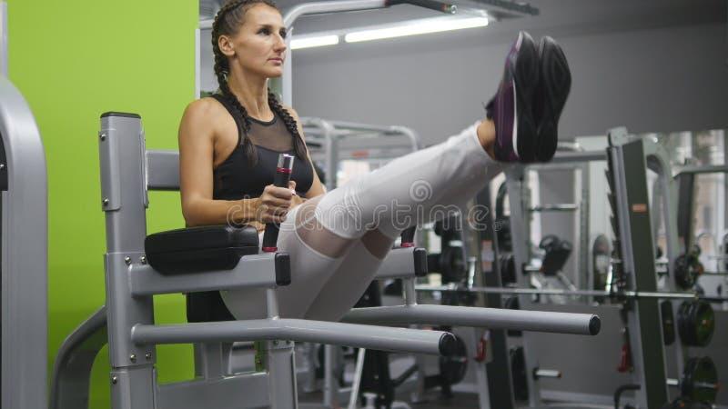 Jeune femme forte avec le corps parfait de forme physique dans les vêtements de sport exerçant des abdominals dans le gymnase For images stock