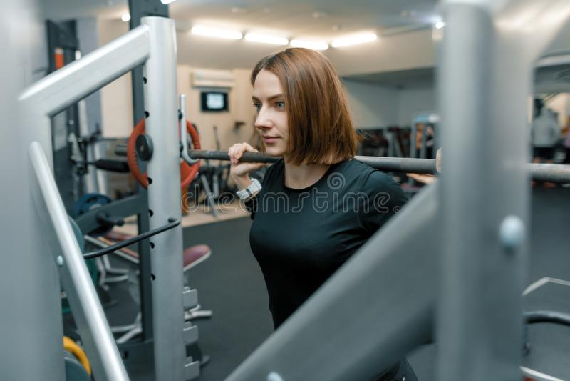 Jeune femme forte de forme physique faisant des exercices de force avec le barbell lourd dans le gymnase de sport Sport, haltérop images stock