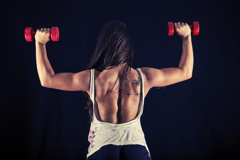 Jeune femme forte faisant la presse de poussée d'haltère photographie stock