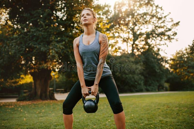 Jeune femme forte s'exerçant avec le kettlebell images stock