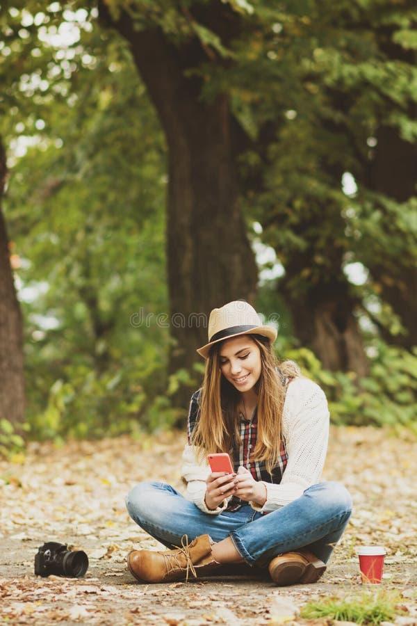 Jeune femme fraîche à l'aide du smartphone dans le parc en automne photos libres de droits