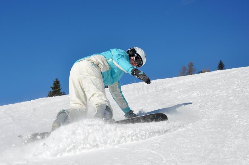 Jeune femme freinant sur le snowboard image stock
