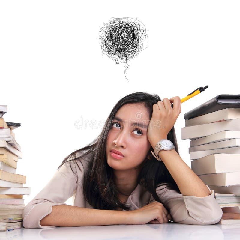 Jeune femme frustrée entre les piles de livres, fond blanc image stock