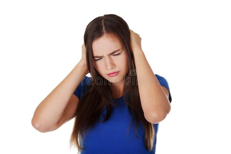 Jeune femme frustrant retenant ses oreilles photos libres de droits