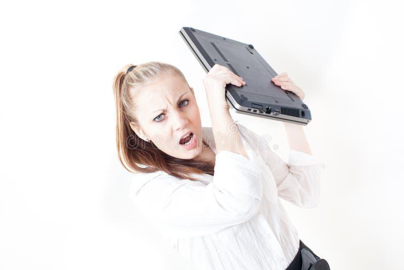 Jeune femme frustrante d'affaires jetant son ordinateur portable image libre de droits