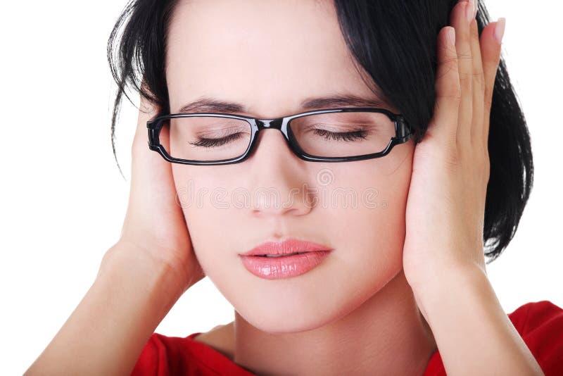 Jeune femme frustrante retenant ses oreilles photos libres de droits
