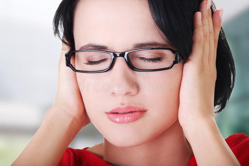 Jeune femme frustrante retenant ses oreilles image stock