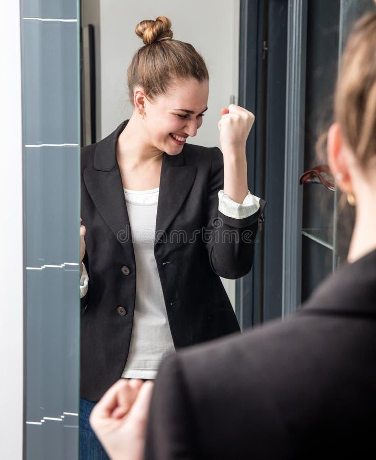 Jeune femme futée enthousiaste disant oui avec les bras joyeux augmentés images stock