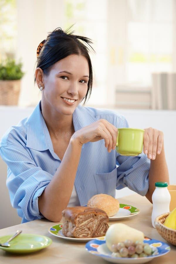 Jeune femme gai prenant le petit déjeuner images stock