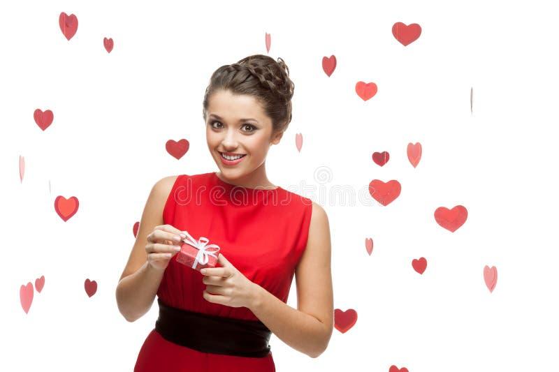 Jeune femme gai retenant le cadeau rouge image stock