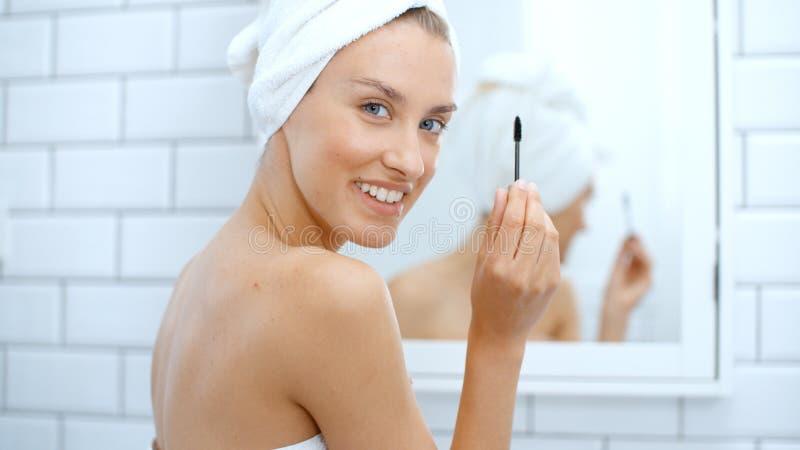 Jeune femme gaie à l'aide du mascara devant un miroir photographie stock libre de droits