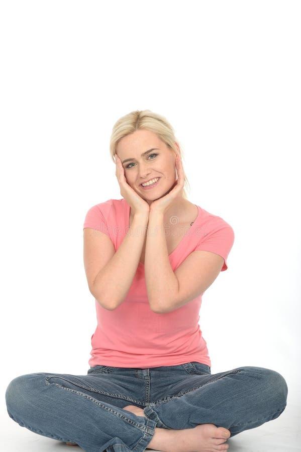Jeune femme gaie attirante heureuse s'asseyant sur le sourire de plancher photos libres de droits