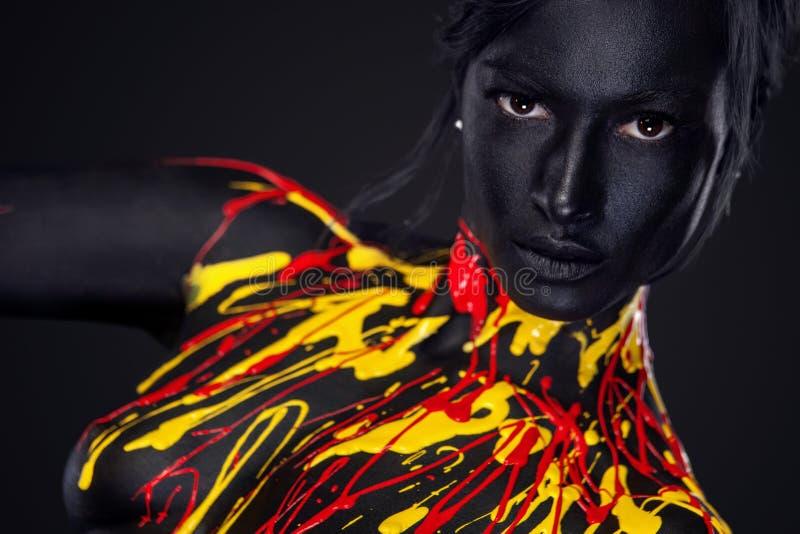 Jeune femme gaie avec le maquillage de mode d'art Une femme étonnante avec le maquillage noir, jaune et rouge de peinture photographie stock libre de droits