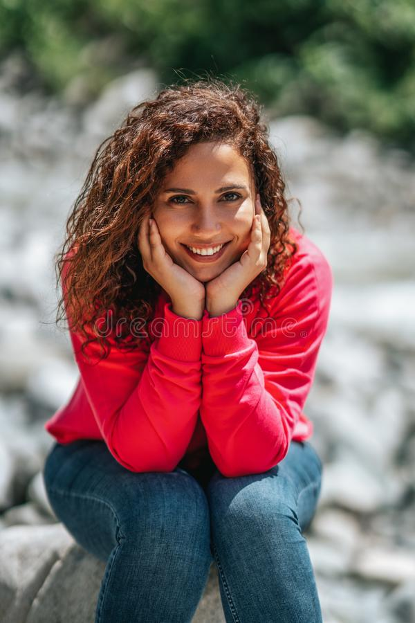 Jeune femme gaie avec les cheveux bouclés posant tout en se reposant dehors images libres de droits