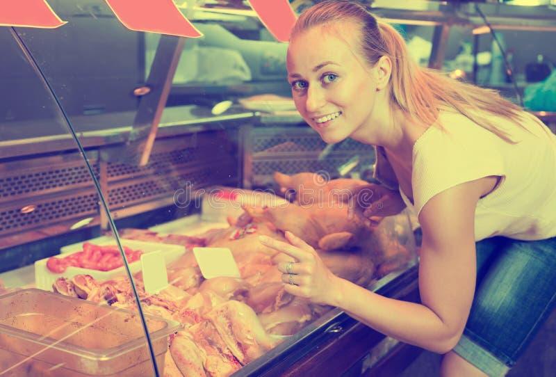 Jeune femme gaie choisissant les pièces fraîches de poulet images stock