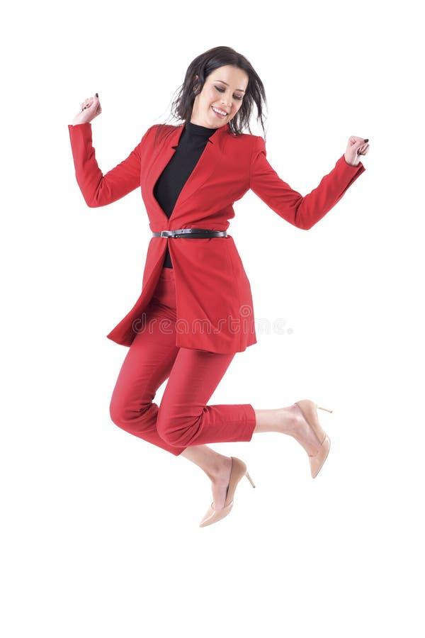 Jeune femme gaie d'affaires dans la robe rouge sautant dans le plein vol regardant vers le bas images stock
