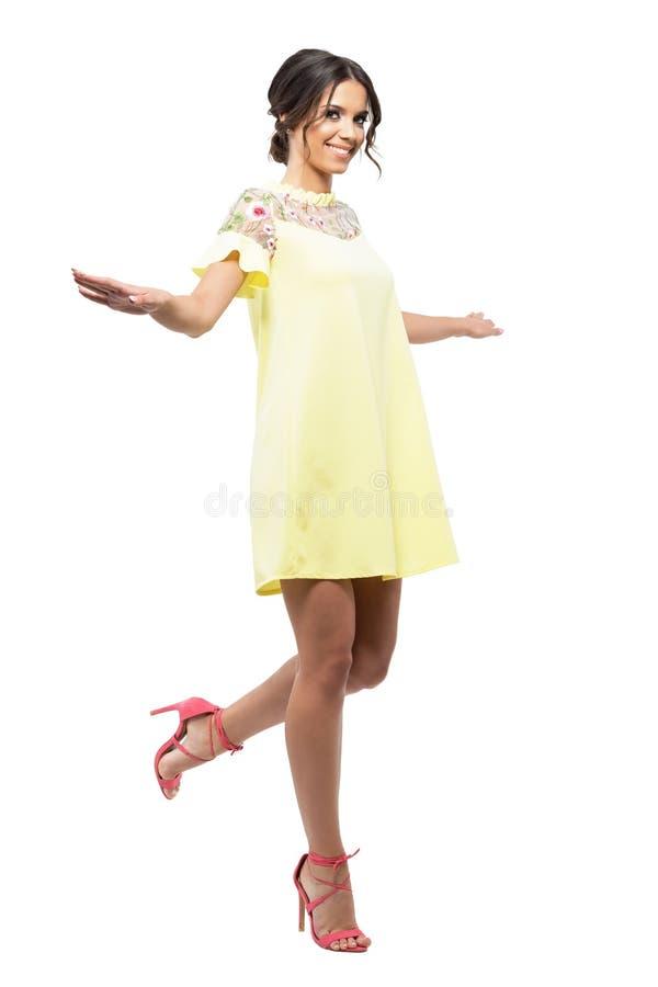 Jeune femme gaie dans la robe jaune de flottement sautant et souriant à l'appareil-photo photo libre de droits