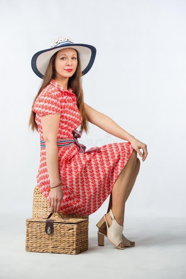 Jeune femme gaie dans la robe rouge avec le panier de picninc dans le studio images libres de droits