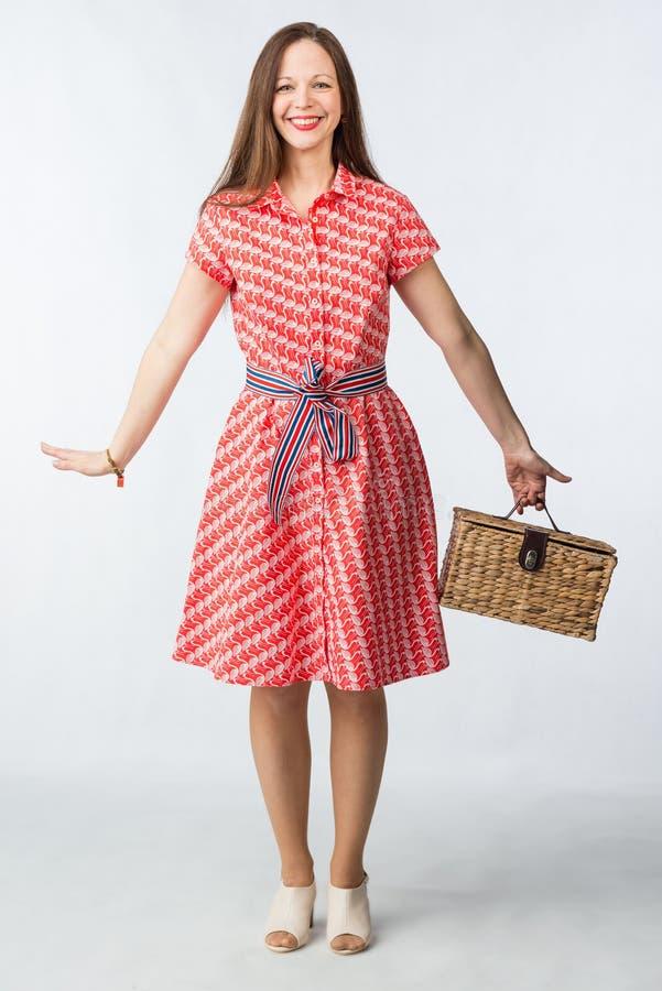 Jeune femme gaie dans la robe rouge avec le panier de picninc dans le studio image stock