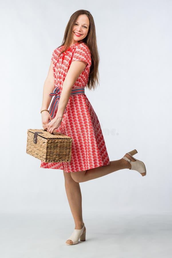 Jeune femme gaie dans la robe rouge avec le panier de picninc dans le studio photo libre de droits
