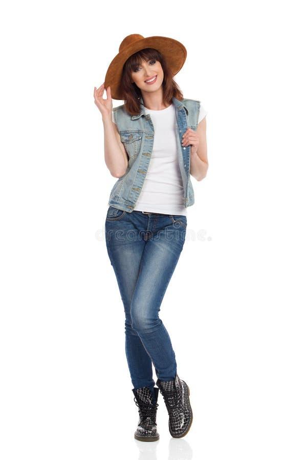 Jeune femme gaie dans le gilet de jeans et le chapeau bleu de suède photographie stock