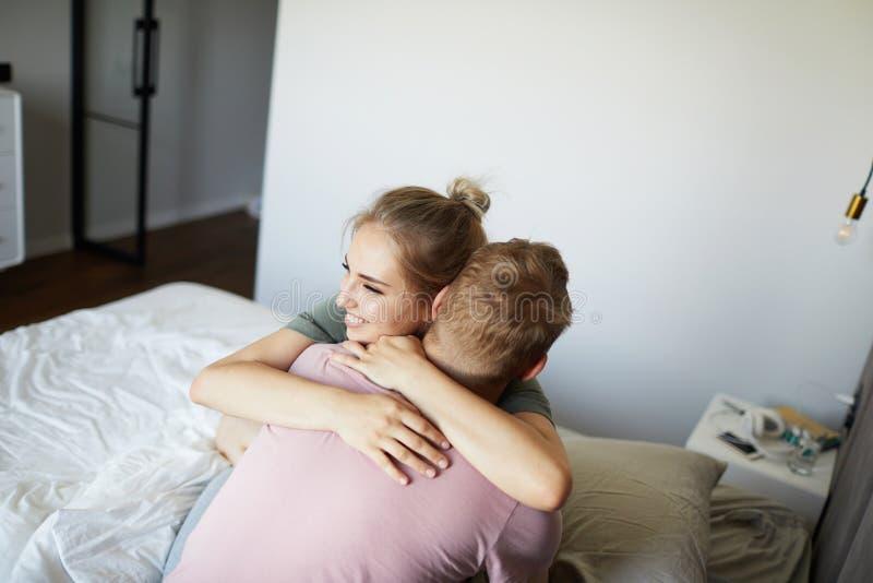 Jeune femme gaie embrassant son mari sur le lit photo libre de droits